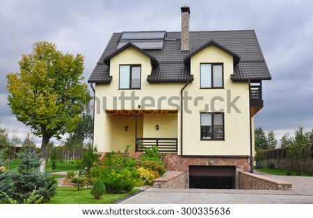 Cozy modern house with beautiful landscaping on a cloudy day. Beautiful house exterior. - stock photo