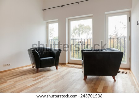 Cozy room with comfortable leather black armchairs - stock photo