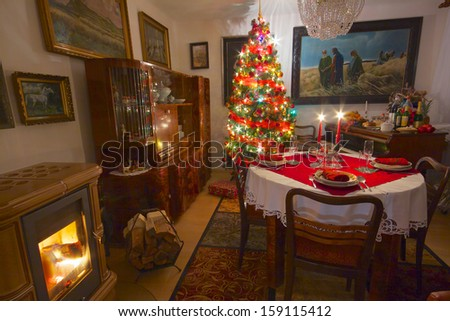 Cozy room with decorated Christmas tree, old piano, fireplace and table ready for Christmas dinner