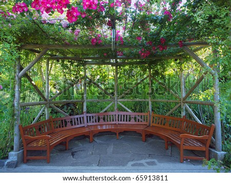 Cozy sitting area in the garden covered with climbing roses - stock photo