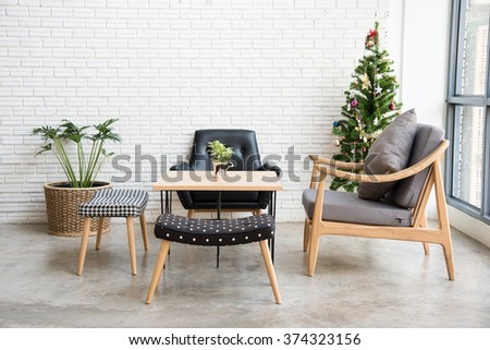 cozy sofa corner with christmas tree decoration at the back. sofa is in modern style and made with wood. - stock photo