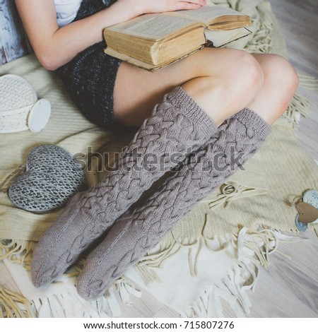Cozy winter evening , warm woolen socks. Woman relaxing at home, reading a book. Comfy lifestyle.