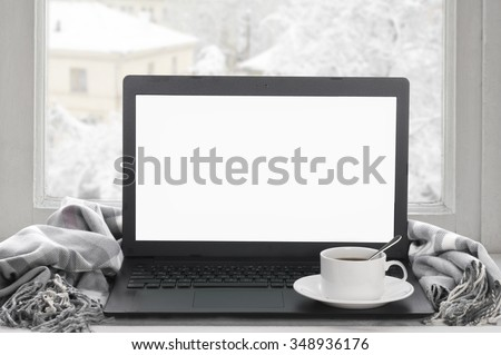 Cozy winter still life: laptop with blank screen, cup of coffee and warm plaid on windowsill against snow landscape from outside. - stock photo