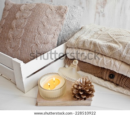 Cozy wool winter accessory. Warm sweaters candle and cone - stock photo