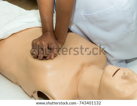 stock-photo-cpr-training-medical-procedure-demonstrating-chest-compression-on-cpr-doll-in-the-class-first-743401132