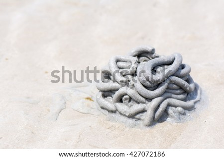 Crab design/Specific made by little crabs on a beach in Rayong, Thailand when removing the excavated sand through tiny sand balls from the holes they dig to lay off eggs,Crab hole on thai beach. - stock photo
