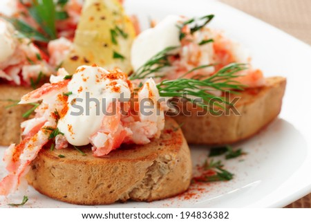 Crab meat with toast, sauce and fresh herbs, close-up - stock photo