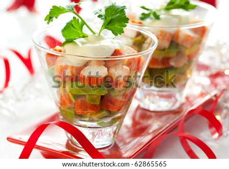 Crab salad with avocado in two glasses . Served on a Christmas table. - stock photo