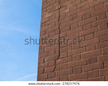 Crack in a brick wall caused by excessive settling due to bad foundations or too much load or earthquake - stock photo