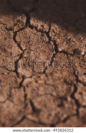 Crack soil on dry season, Global warming effect. Closeup macro artistic blurred background.