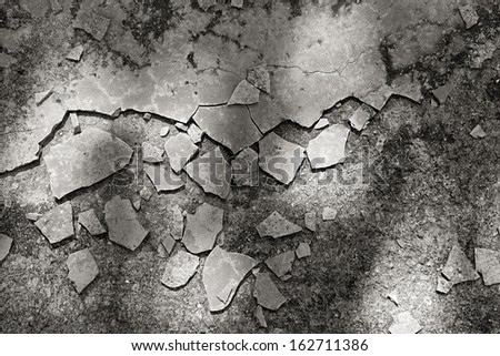 Cracked and broken cement paving lying scattered randomly on the ground in dappled shadow