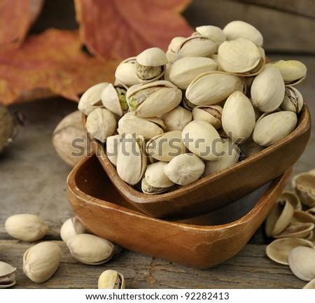 Cracked and Dried Pistachio Nuts In A Wooden Bowl
