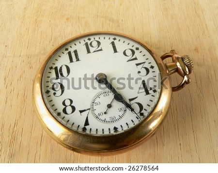 cracked and dusty antique pocket watch on wooden surface - stock photo