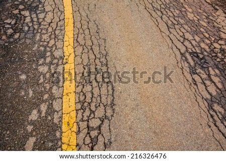 Cracked asphalt road with yellow lines - stock photo