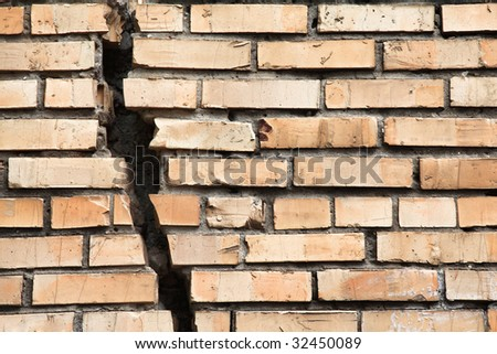 cracked brick wall - stock photo