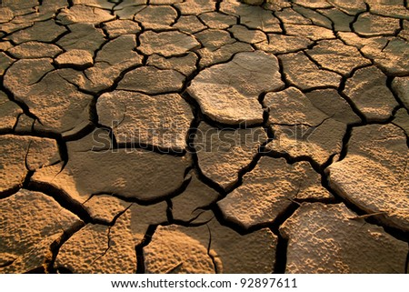 Cracked by the heat long lifeless soil - stock photo
