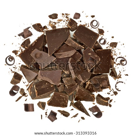 Cracked chocolate pile and curls top view on white background - stock photo