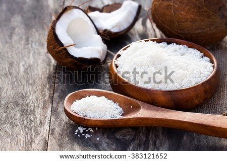 Cracked  coconut and flakes on rustic wooden table background  - stock photo