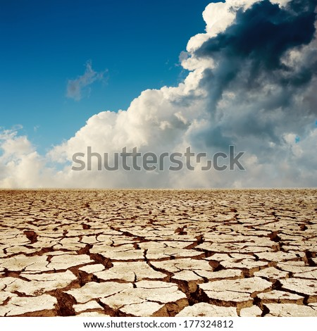 cracked earth and dramatic sky - stock photo