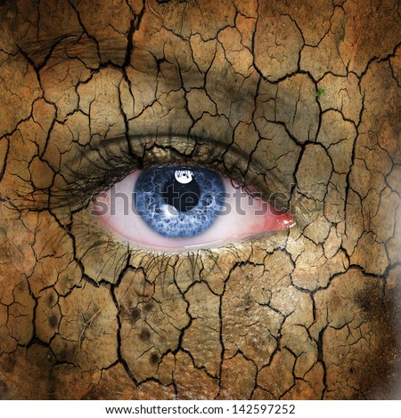 Cracked earth pattern on human face with blue eye. - stock photo