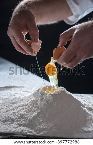 Cracked egg falling into a pile of flour