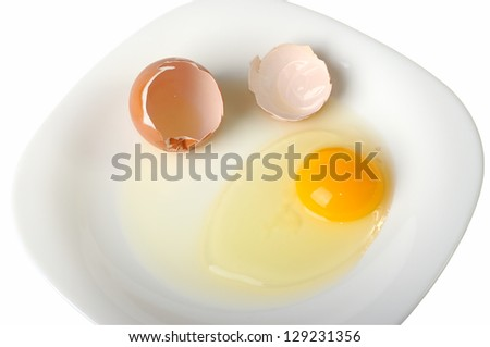 Cracked egg on a black plate
