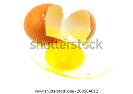 cracked egg with yolk on white isolate - stock photo
