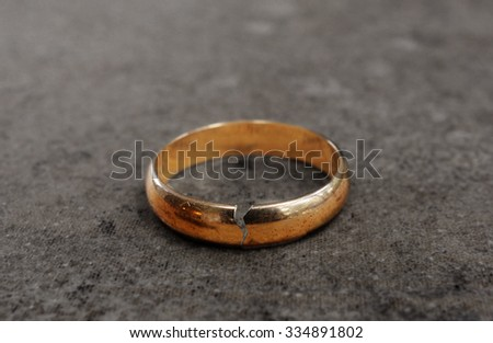 Cracked gold wedding ring -- divorce concept                                - stock photo