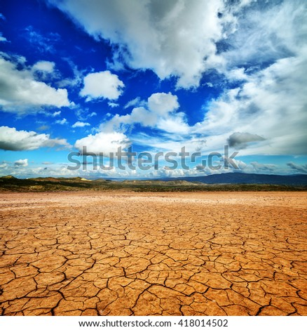 Cracked ground and cloudy scay. Natural disaster landscape - stock photo