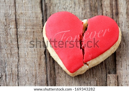 Cracked heart shaped cookie decorated with red icing and the word Forever as a concept of broken heart, breakup and end of relationship - stock photo