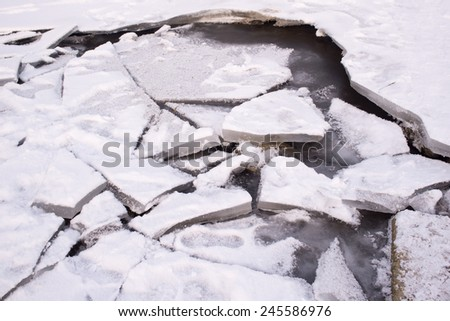 Cracked ice on the river in winter - stock photo