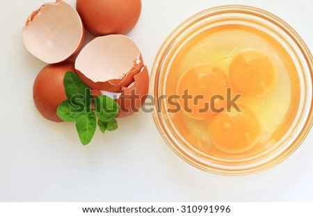 cracked raw eggs yellow sunny yolks culinary bowl brown eggshell fresh basil herb ingredients healthy breakfast cooking light background soft focus - stock photo