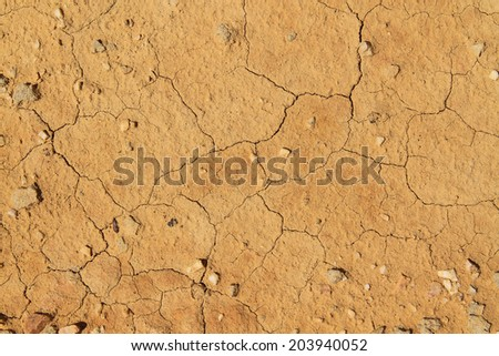 Cracked red dirt soil field  - stock photo