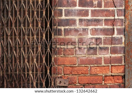 Cracked urban brick wall bordered by rusty metal has multiple patterns and textures for use as background. - stock photo