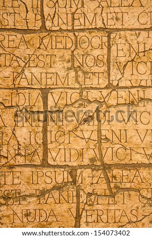 Cracked wall with Latin inscriptions and Roman letters, marble background.  - stock photo