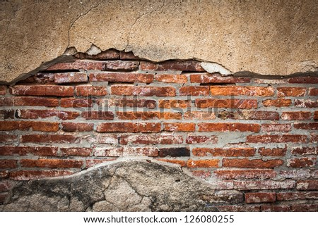 Cracked wall with orange bricks inside