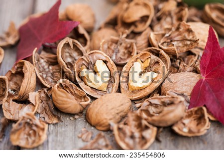 Cracked walnuts on wooden background, close up. Heart shape. - stock photo
