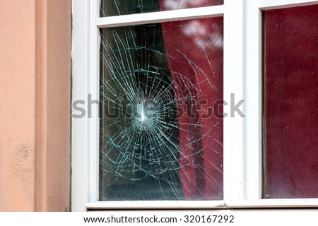 Cracked window in the old house - stock photo