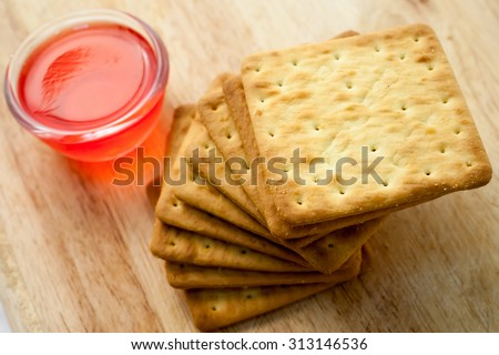 Cracker and coffee or tea on wood background - stock photo