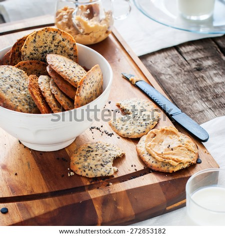 Cracker Cookies with Black Sesame Seeds and Peanut Butter as breakfast on the wooden chopping board - stock photo