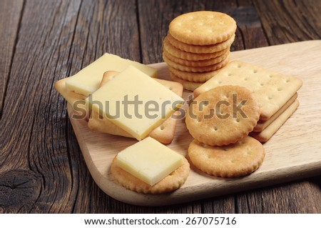 Cracker cookies with cheese on wooden cutting board