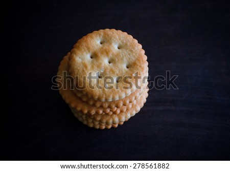 cracker put on black wooden table, image dark tone - stock photo