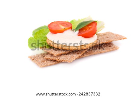 Crackers stacks with fresh vegetables and cream isolated on white background.