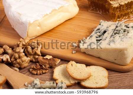 Crackers, white cheese and honey on wooden background in studio photo