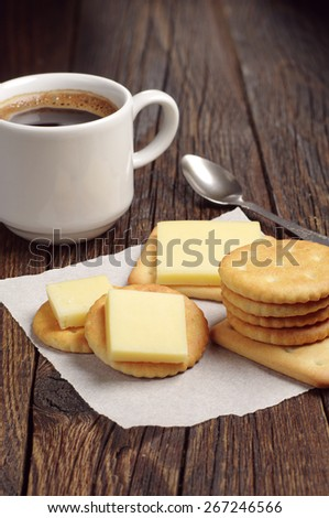 Crackers with cheese and coffee cup on rustic wooden table - stock photo