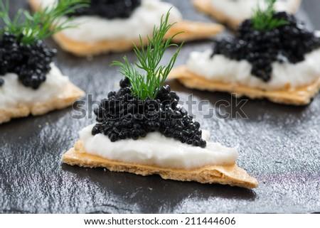 crackers with cream cheese and black caviar, horizontal - stock photo