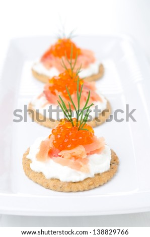 crackers with cream cheese, salted salmon and red caviar on the white plate - stock photo