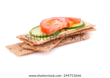Crackers with fresh vegetables and cheese isolated on white background. - stock photo