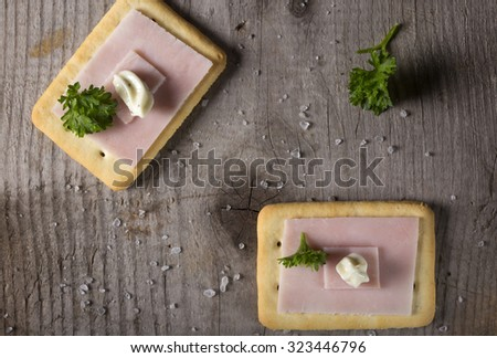 Crackers with ham and roumulade sauce on dark wood tabletop with parsley and salt - stock photo