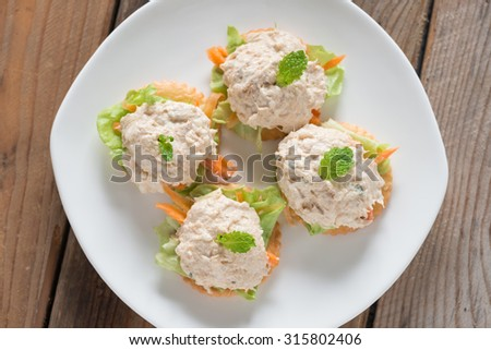 Crackers with tuna salad on white plate. Top view. - stock photo
